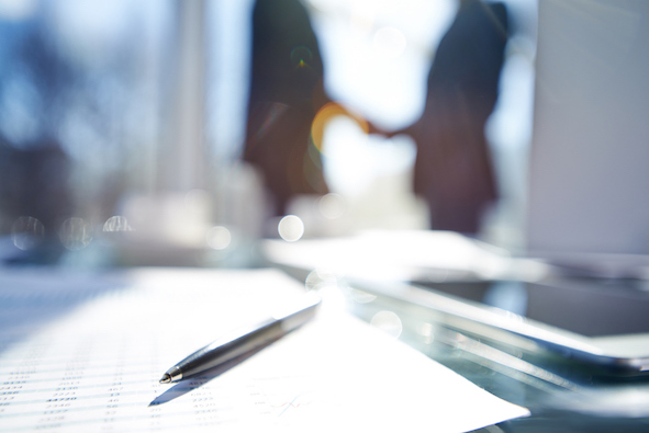 Document and pen on the desk, silhouettes of business people shaking hands in the background